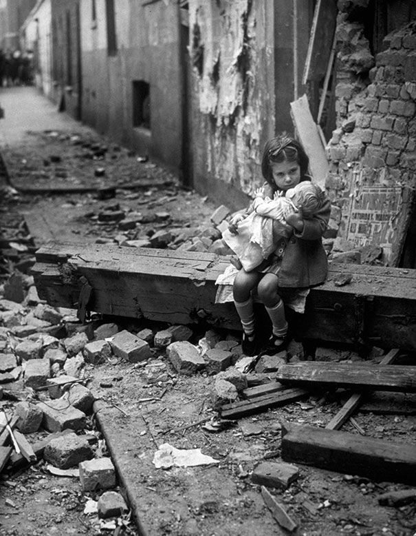 1940_Little_girl_with_her_doll_sitting_in_the_ruins_of_her_bombed_home_London