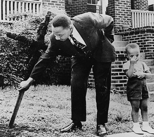 1960_Martin_Luther_King_with_his_son_removing_a_burnt_cross_from_their_front_yard