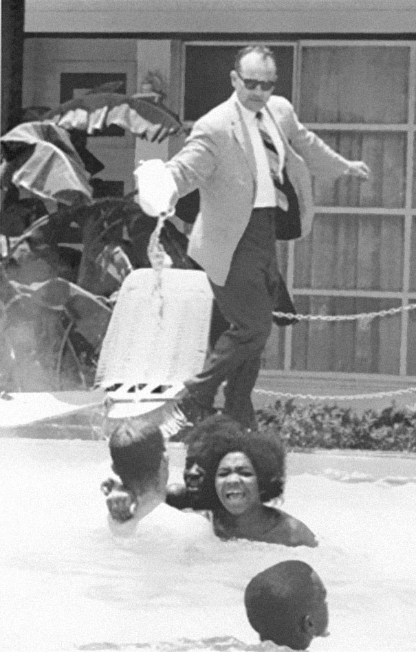 1964ca_Hotel_owner_pouring_acid_in_the_pool_while_black_people_swim_in_it